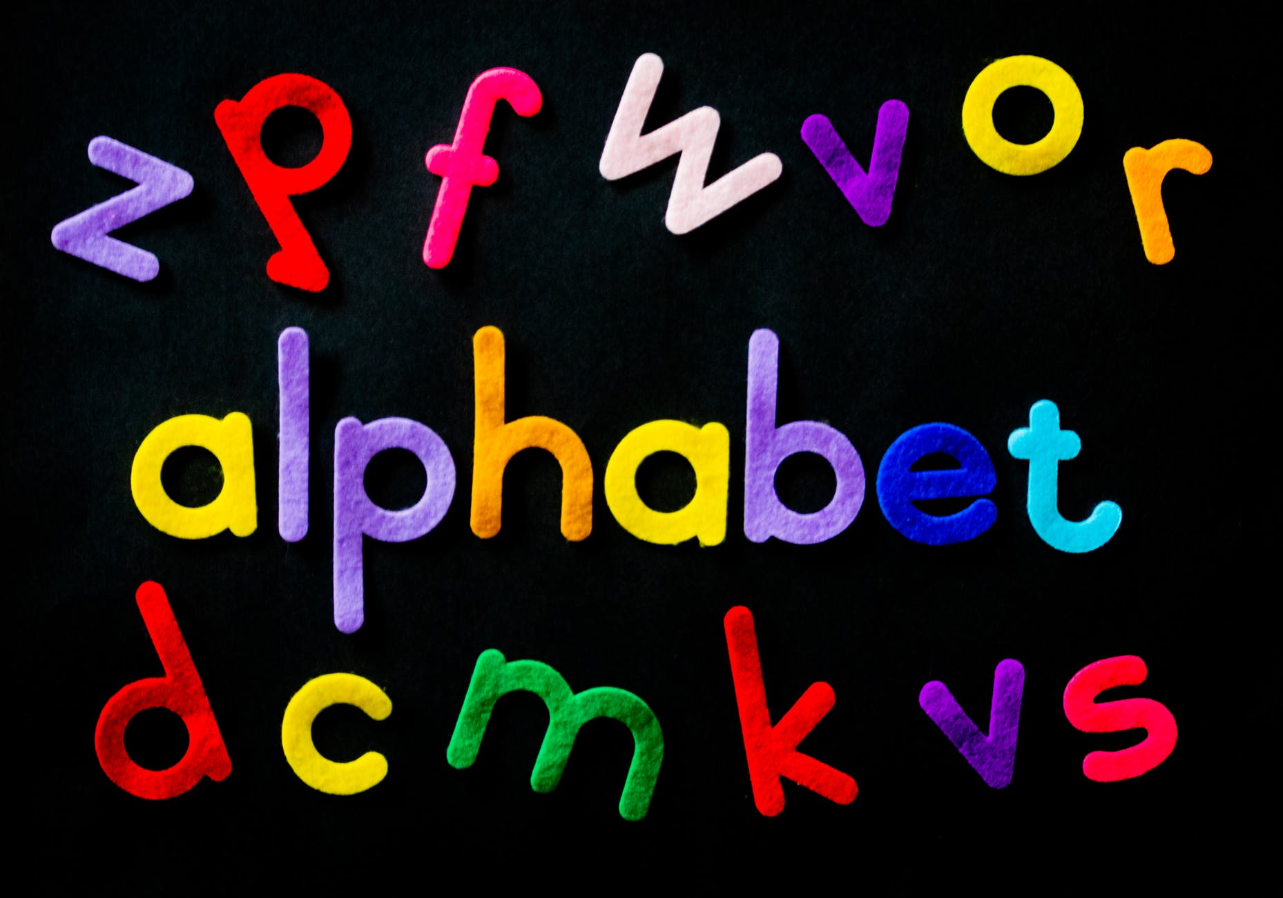 assorted color alphabet on black background